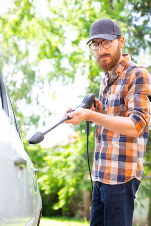 Cleaning a car in the garden with a high pressure washer.