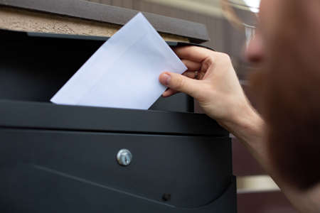 Sending, receiving mail. Young man putting a letter in a white envelope into a home stainless, black, metal mailbox. Traditional mail in a letterbox, correspondence. Postman. Stock Photo