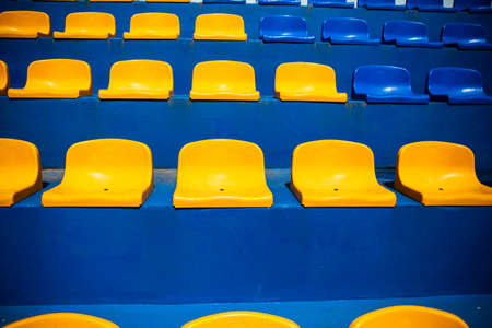 Blue and yellow plastic seats at the local soccer, football stadium. Grandstands, stands at the city sport stadium without a roof. Club colors. Tribune with chairs for fans at sport event, front view