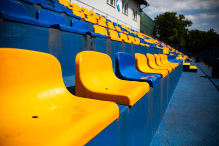 Colored plastic seats at the local soccer, football stadium. Grandstands, stands at the city sport stadium without a roof. Blue and yellow club colors. Tribune with chairs for fans at a sport event