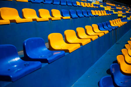 Several rows of plastic, blue and yellow seats at a local soccer, football stadium. Grandstands, stands at the city sport stadium without a roof. Club colors. Tribune with chairs for fans.