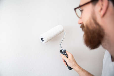 Wall painting in white color with a paint roller in a bright room, close-up. Self apartment renovation, house repair works, walls and ceilings painting - a paint roller in a house painter's hand.