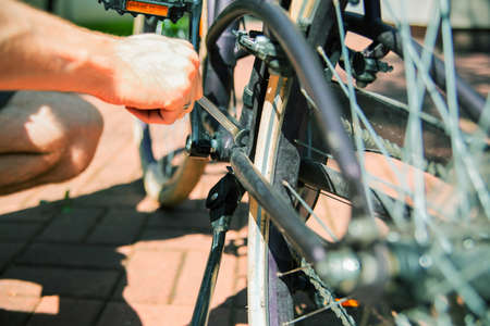 Repairing a bicycle, changing a wheel, an inner tube with a hand tool, outdoor on a sunny day. Banque d'images