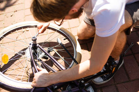 Man repairing a bicycle, changing a wheel, an inner tube with a hand tool, outdoor on a sunny day.