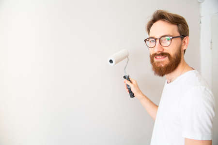 Young man painting wall in white with a paint roller in a bright room. Self apartment renovation, house repair works, walls painting - a house painter at work, looking at camera, with a copy-space.