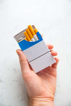 Full pack of cigarettes in a hand of a young adult man