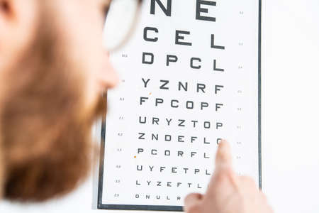 Reading an eye test chart on a white wall, close-up. An ophthalmologist, an optometrist eye examination. A vision test board, a test for visual acuity. Zdjęcie Seryjne
