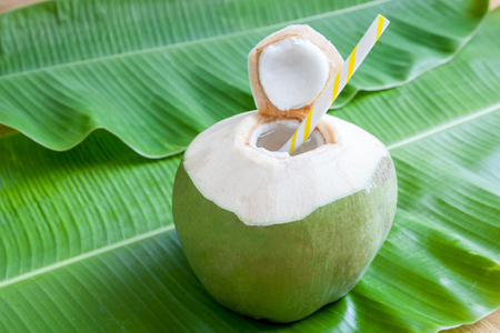 Sweet green coconut water with drinking straw on banana leaf.