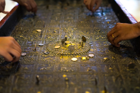 People try to put coin on Buddhas footprint statute.