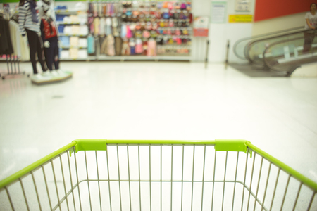 Cropped image of  green shopping cart with blur background.