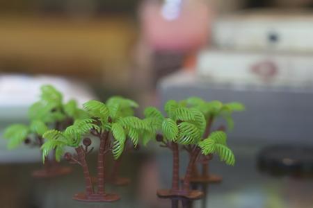 Plastic palm tree toys on background blur.