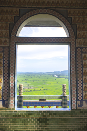 Tile window frame with green field out side. Archivio Fotografico