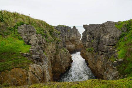小峡谷在薄煎饼岩石与绿色银行