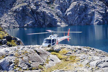 Running helicopter landed on rocks - lake in background on Mt. Kidd