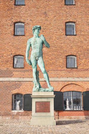 replica statue of Michelangelo's David next to brick building 'Westindian storehouse', Copenhagen, Denmark Editoriali