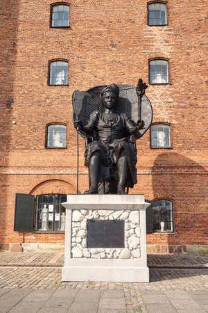 statue of Mary Thomas aka Queen Mary next to brick building 'Westindian storehouse', Copenhagen, Denmark