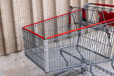 A silver and red metal shopping cart parked against a beige wall outside a supermarket in London, Ontario, Canada on a gloomy and overcast day winter day