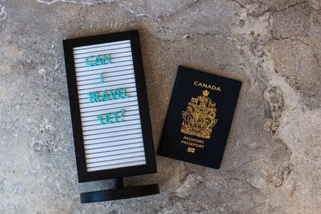 Message board, 'can I travel yet' and Canadian passport on a marble backdrop, Canada, Ontario.