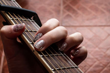 A woman with glitter nail polish plays an A minor chord on an accoustic guitar, fitted with a capo.