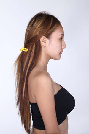 moles: Asian Woman before make up hair style. no retouch, fresh face with acne, skin moles with strapless bra. Studio lighting white background, Side view of head