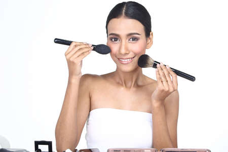 exact position: Asian Tan Skin Woman with Hand On Present by each type size of Make up Brush from different 14 pcs set on exact position of each specific brush, studio lighting white background isolated copy space