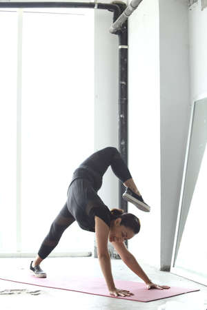 forearms: Asian Woman Yoga Teacher Instructor demonstrate lesson on matte, black dress suite leotard fashion legging, full length in high exposure window sun light and mirror reflection herself