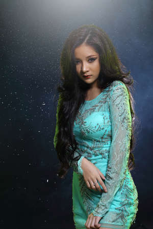 love blow: Beautiful Asian Girl in Glitter, Snowflake and Smoke in Dark background, half body portrait, lady black hair in green lace embroidery evening ball gown dress Stock Photo