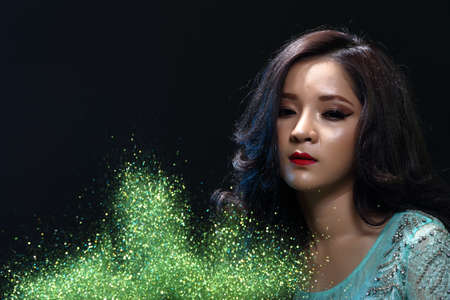 love blow: Beautiful Asian Girl in Green Glitter, Snowflake and Smoke in Dark background, half body portrait, lady black hair in green evening ball gown dress Stock Photo