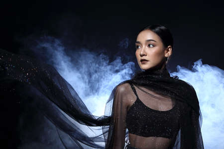 hair wrapped up: Asian Femaile Model in Dark environment with fog smokey back light wrapped black hair style fashion make up, portrait half body