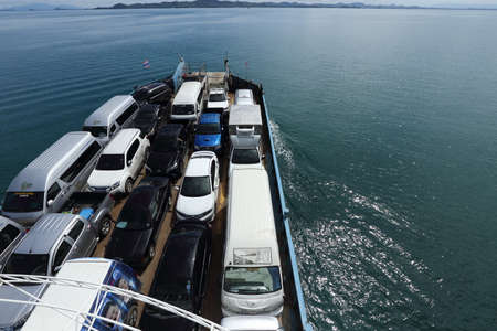 carrying: Trat, Thailand - July 3, 2017 ;  Ferry Carry car vehicles acroos Thai Bay to Koh Chang Island in beautiful sunshine day green ocean Editorial