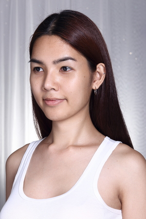 Asian Woman transgender before make up brunette hair style. no retouch, fresh face with nice and smooth skin. Studio lighting grey background, portrait Stock Photo
