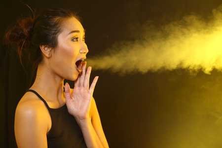 Smoking Tan Skin Asian Woman black hair dark lip with Yellow Dense Fluffy Puffs of Smoke and Fog on dark Background, Abstract Smoke Clouds, and high low exposure contrast