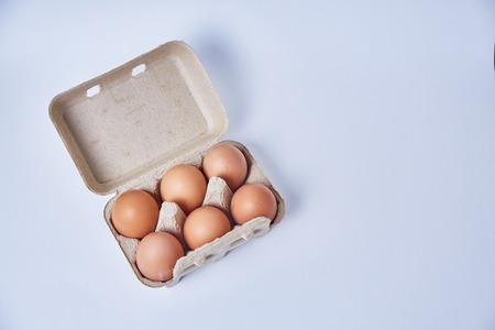Sechs Eier in Papier-Box auf weißem Hintergrund Standard-Bild - 71650702