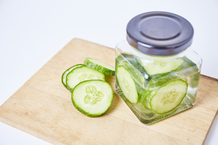 Cucumber sliced pickle in bottle on white background