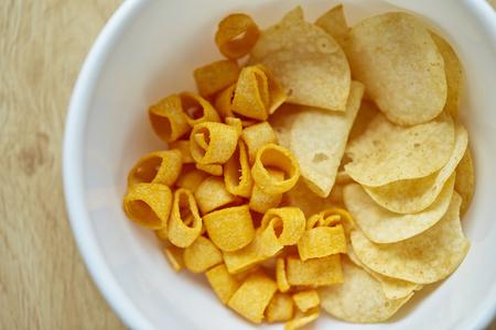 Crispy potato chips in white bowl