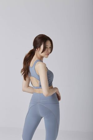 Asian girl wear exercise suit pose her back body in studio