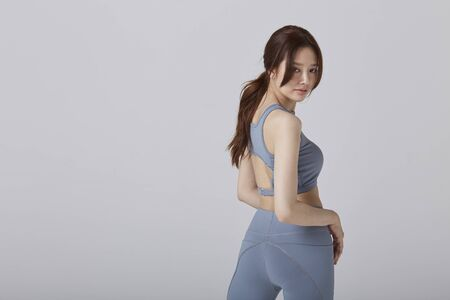 Asian girl wear exercise suit pose her back body in studio 版權商用圖片