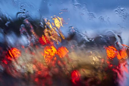 Abstract blurred traffic car light with rain on clear mirror
