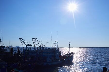 Silhouette fishing boat with sunny sky Stock Photo