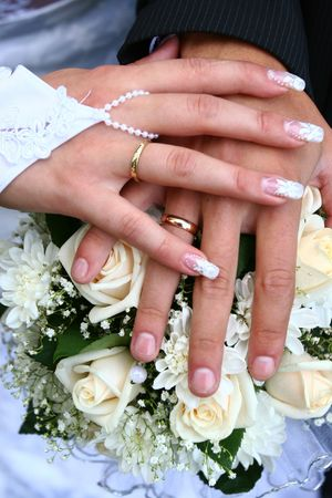Hands of the groom and the bride with rings lie on a white bunch of flowers photo