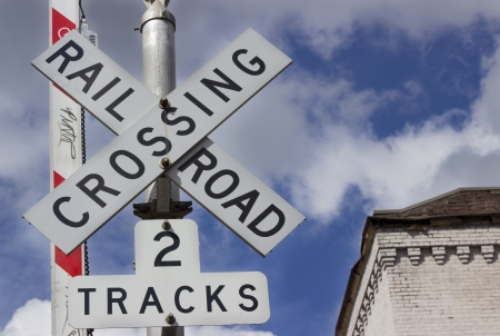 A railroad crossing sign with a blue sky background