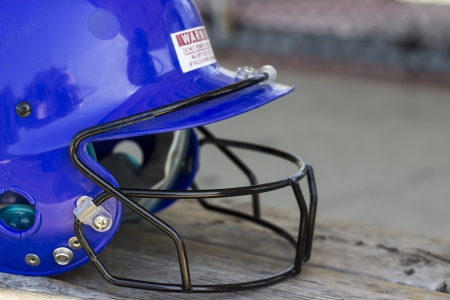 A blue batting cage helmet sitting on a bench photo
