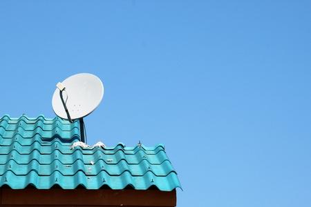 antena parabolica: Un plato blanco en el techo azul en el norte de Tailandia