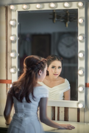 front of: Young asia beautiful woman standing front of mirror in room