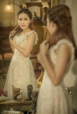 woman mirror: Young asia beautiful woman standing front of mirror in room