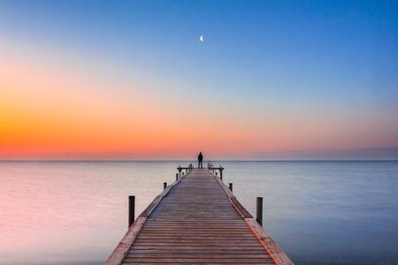 verano: Un hombre de pie al final de un muelle mirando la luna al amanecer