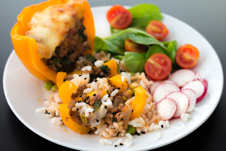 peppar: Cooked yellow peppar with meat beef, rice, vegetables, tomatoes, spinach, radish, black caraway seeds Stock Photo