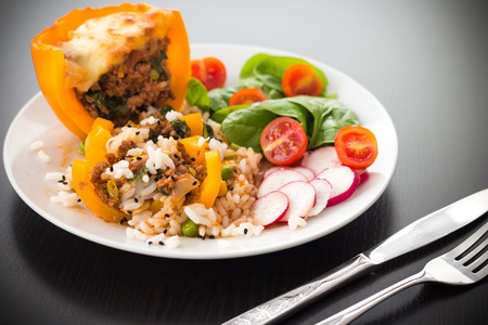 caraway: Cooked yellow peppar with meat beef, rice, vegetables, tomatoes, spinach, radish, black caraway seeds Stock Photo