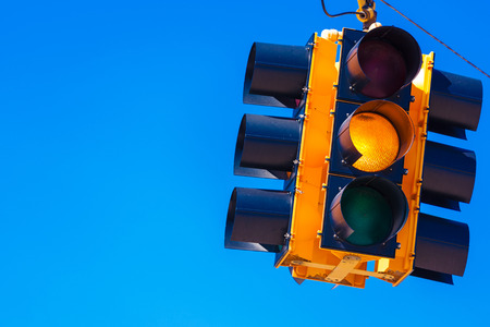 A yellow traffic signal with a sky blue background