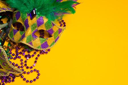 マルディグラのカーニバル マスク黄色背景に陽気でカラフルなグループ。 ベネチアン マスク。